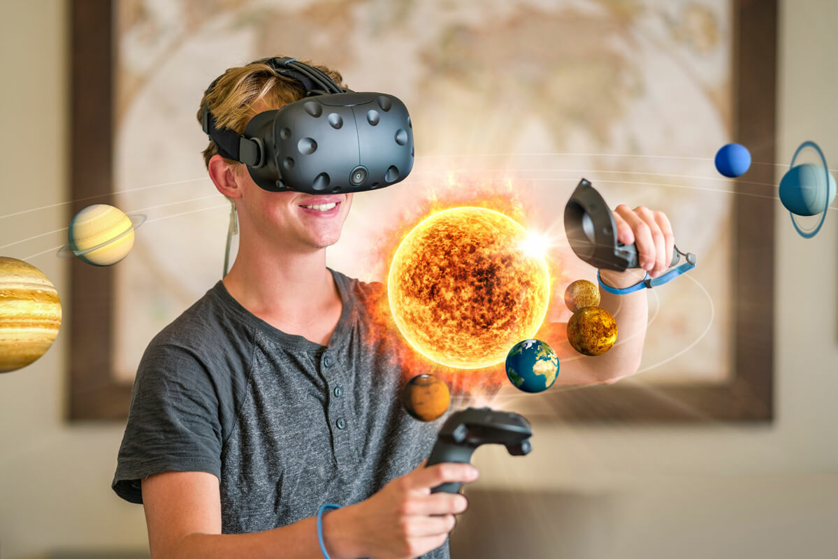 Male student explores the solar system with a HTC Vive virtual reality headset